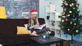 Elegante Frau im Sankt-Hutlesebuch, das auf Sofa auf Weihnachten sitzt stock video footage