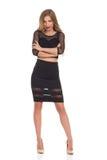 Elegante Frau im schwarzen Kleid, das mit den Armen gekreuzt steht Stockbilder