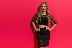 Elegante Frau im schwarzen Kleid, das weg schaut Lizenzfreie Stockfotos