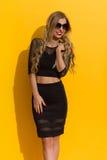 Elegante Frau im schwarzen Kleid gegen gelben Sunny Wall Stockbilder