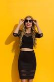 Elegante Frau im schwarzen Kleid und in der Sonnenbrille, die oben schaut Lizenzfreie Stockfotos