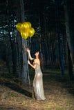 Elegante Frau mit Ballonen im Wald stockfotografie