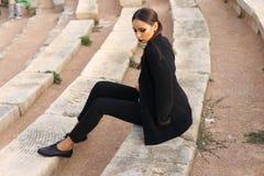 Elegante Frau mit dem dunklen Haar, das ein weißes Hemd und schwarzen Hosen trägt stockfoto