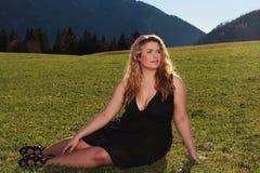 Elegante Frau mit der übergroßen Hälfte, die auf einer Wiese in den Alpen liegt Lizenzfreie Stockfotos