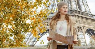 Elegante Frau mit der Karte, die den Abstand in Paris untersucht Stockfoto