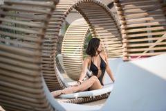 Elegante Frau mit einem perfekten Körper, der im Profil auf einem hölzernen Ruhesessel auf dem Luxus-Resort sitzt Stockfotos