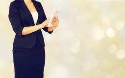 Elegante Frau Younf im Anzug, der Tablette vor glamourus bokeh hält, beleuchtet Hintergrund Stockbilder