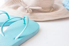 Elegante Frauen Straw Sun Hat mit Bogen-blauem Strand Flip Flops auf weißen Hintergrund-Küsten-Ferien stockfotos