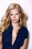 Elegante freundliche schöne blonde Frau mit dem langen gelockten Haar und gewinnendem Lächeln Lizenzfreies Stockfoto