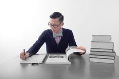 Elegante Geek: mens die op blocnote, met open boek en stapel boeken op bureau schrijven Royalty-vrije Stock Foto's