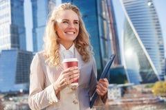 Elegante Geschäftsfrau in der beige Jacke während des Bruches mit Kaffee stockbilder