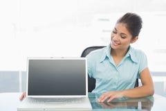 Elegante Geschäftsfrau mit Laptop auf Schreibtisch im Büro Lizenzfreie Stockfotos