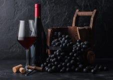 Elegante glas en fles rode wijn met donkere druiven binnen uitstekend houten vat op zwarte steenachtergrond Natuurlijk Licht royalty-vrije stock afbeeldingen
