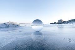 Elegante Glaskugel auf Eis auf einem gefrorenen See stockfotografie