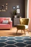 Elegante groene leunstoel en een blauwe deken met patroon op hardhoutvloer in een donkergrijs woonkamerbinnenland met een roze ba stock foto