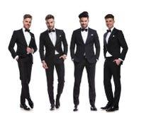 Elegante Gruppe von vier Männern, die mit den Händen in den Taschen stehen Lizenzfreie Stockfotos