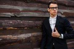 Elegante, hermoso, hombre en el traje clásico, presentando cerca de la pared de madera imagen de archivo libre de regalías