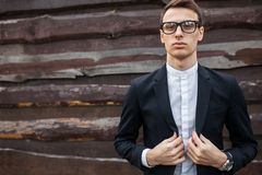 Elegante, hermoso, hombre en el traje clásico, presentando cerca de la pared de madera imagen de archivo