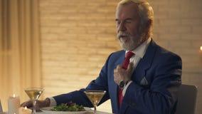 Elegante hogere heer die tijd controleren die op horloge, vrouw in restaurant wachten stock videobeelden