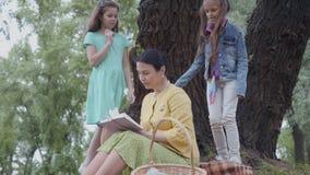 Elegante hogere vrouwenzitting op de deken onder de boom in het park die het boek lezen Twee het leuke kleindochters proberen stock footage