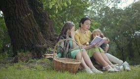 Elegante hogere vrouwenzitting op de deken onder de boom in het park die het boek lezen Twee het leuke kleindochters zitten stock footage