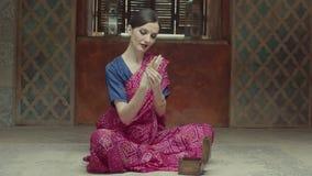 Elegante indische Artfrau, die an Armbänder setzt stock video