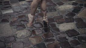 Elegante jonge balletdanser middeleeuwse straat onder de regen Het stappen op uiteindetenen in pointe Sluit omhoog van een baller stock footage