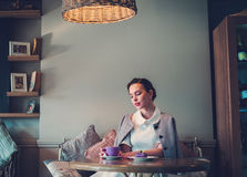 Elegante jonge dame alleen in een koffie stock fotografie