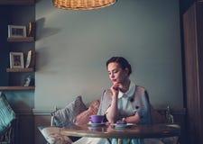 Elegante jonge dame alleen in een koffie stock foto's