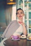 Elegante jonge dame alleen in een koffie stock afbeelding