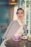 Elegante jonge dame alleen in een koffie stock afbeeldingen