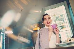 Elegante jonge dame alleen in een koffie stock foto