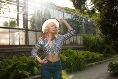Elegante jonge dame die hoed en het in uitrusting stellen dragen dichtbij Stock Foto