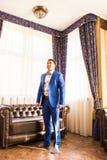 Elegante jonge mens die klaar worden kledende kostuum, overhemd en manchetten stock foto's