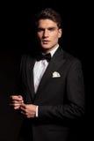 Elegante jonge mens die zijn koker bevestigen Stock Afbeelding
