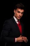 Elegante jonge mens in kostuum, die zijn jacke bevestigen Royalty-vrije Stock Afbeeldingen