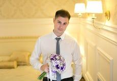 Elegante jonge mens met een boeket van bloemen stock foto's