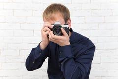 Elegante jonge mens met oude zeldzame fotocamera op witte baksteenrug Royalty-vrije Stock Afbeeldingen