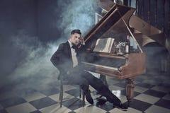Elegante jonge mens met piano stock foto's