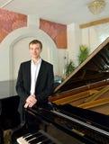 Elegante jonge pianist naast grote piano Royalty-vrije Stock Fotografie