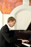 Elegante jonge pianistspelen op grote piano Royalty-vrije Stock Afbeeldingen
