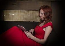 Elegante jonge roodharigevrouw in een rode kledingszitting op de laag en het bekijken PC-tablet Stock Afbeeldingen
