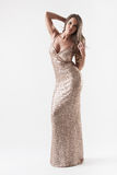 Elegante jonge vrouw in modieuze gouden avondjurk Stock Foto