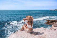 Elegante jonge vrouwenzitting door de oceaan stock foto