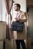 Elegante jonge zakenman die uit het venster kijken. royalty-vrije stock afbeeldingen