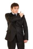 Elegante jonge zakenman die zijn kostuum borstelt Stock Afbeelding