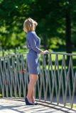 Elegante junge blonde Dame, welche die Sonne auf der Brücke betrachtet Lizenzfreies Stockbild
