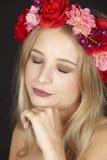 Elegante junge blonde Frau mit Blumenkranz in ihrem Haar Stockfotografie