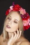 Elegante junge blonde Frau mit Blumenkranz in ihrem Haar Stockbild