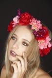 Elegante junge blonde Frau mit Blumenkranz in ihrem Haar Lizenzfreies Stockbild